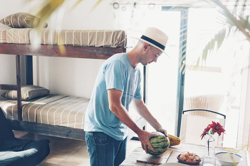 Young man holding fruits at home