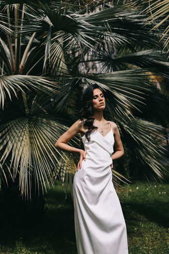 Elegant sensual woman brunette bride in a silk wedding dress posing among palm trees in the park
