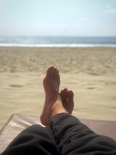 Low Section Of Man Relaxing On Lounge Chair At Beach