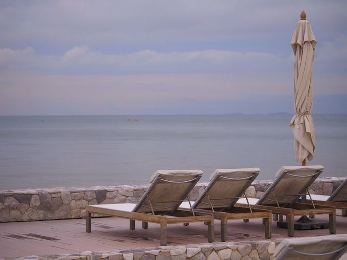Rear view of sun loungers against calm sea