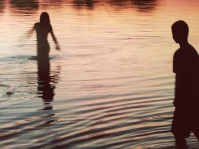 Silhouette people standing in water