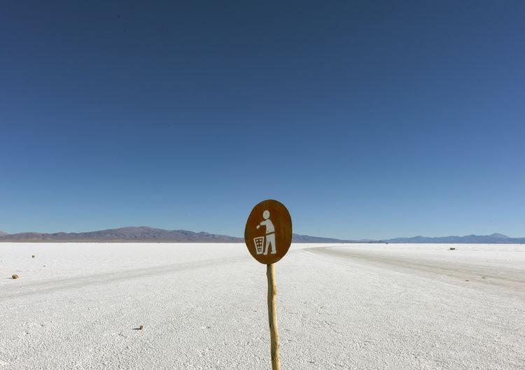 Road sign against clear blue sky salt desert