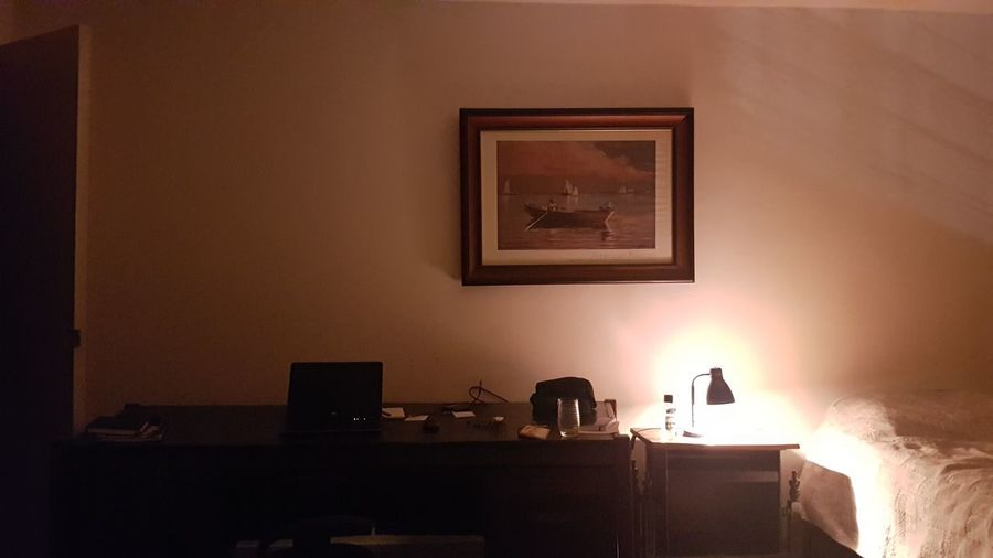 Illuminated electric lamp on table by wall at home