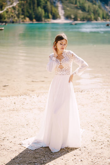 Full length of bride standing at riverbank