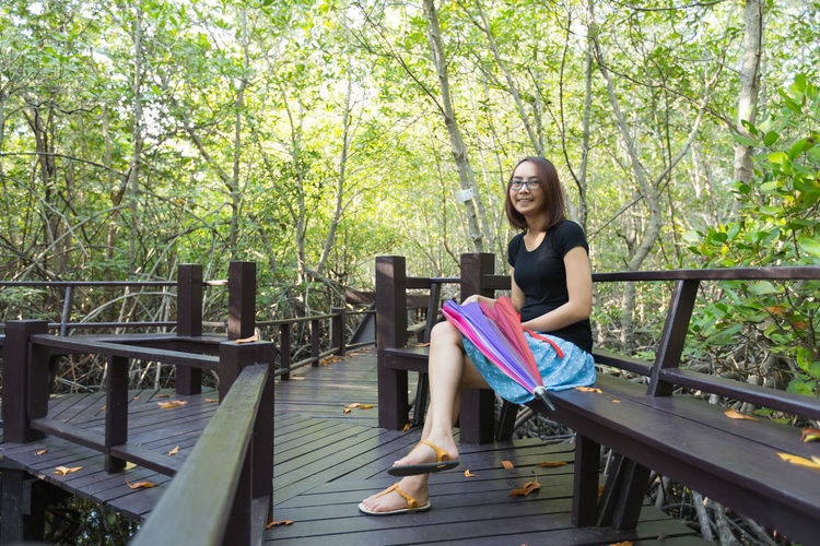 Young woman sitting on bench on boardwalk against trees in park