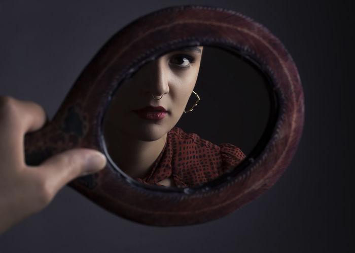 Close-up portrait of woman holding cigarette over black background