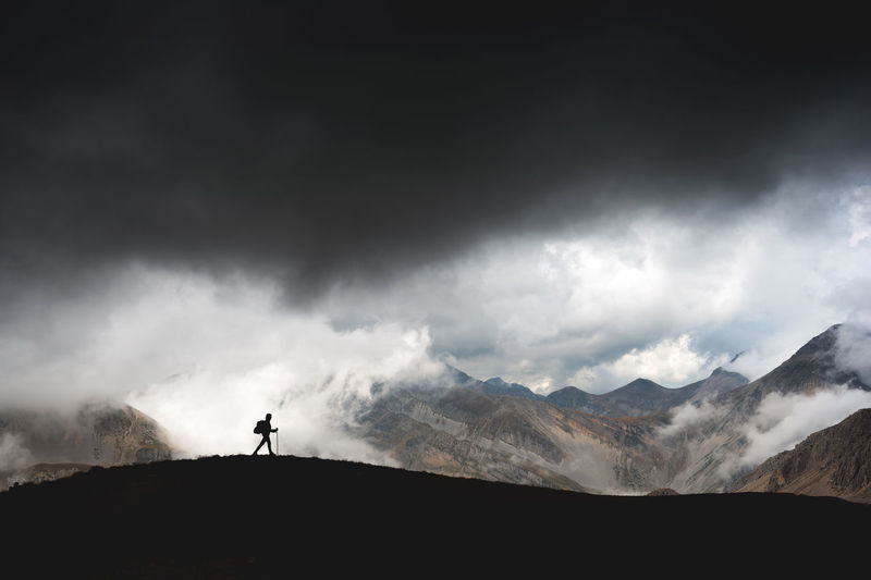 Silhouette person standing on mountain against sky