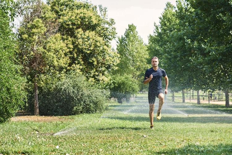 Full length of man running on street amidst trees