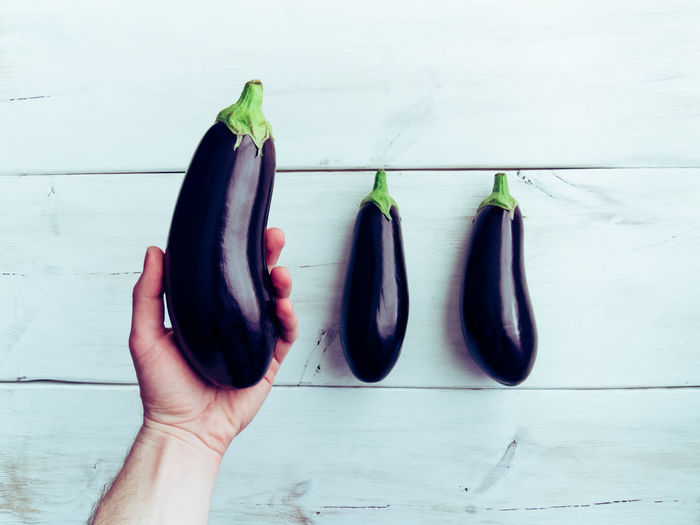 Cropped Hand Of Man Holding Eggplant Over Table