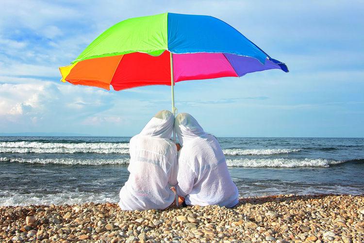Rear view of umbrella on beach