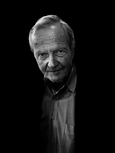 Portrait of senior man against black background