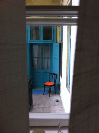 Blue door, empty chair Blue Door Blue Window Brown Chair Building Exterior Closed Curtain Empty Fence Glass House Neighborhood Neighbour No People Old Orange Chair Orange Pillow Window Window Frame Window Shade Lieblingsteil