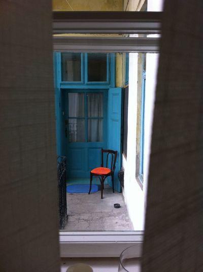 Blue door, empty chair Blue Door Blue Window Brown Chair Building Exterior Closed Curtain Empty Fence Glass House Neighborhood Neighbour No People Old Orange Chair Orange Pillow Window Window Frame Window Shade Lieblingsteil