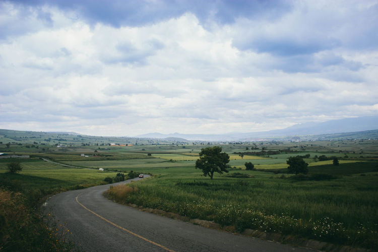 Agriculture Beauty In Nature Cloud - Sky Day Escape Grass Green Color Growth Highway Horizon Idyllic Landscape Mountain Nature No People Outdoors Road Road Scenics Sky Tranquil Scene Tranquility Travel Tree Village