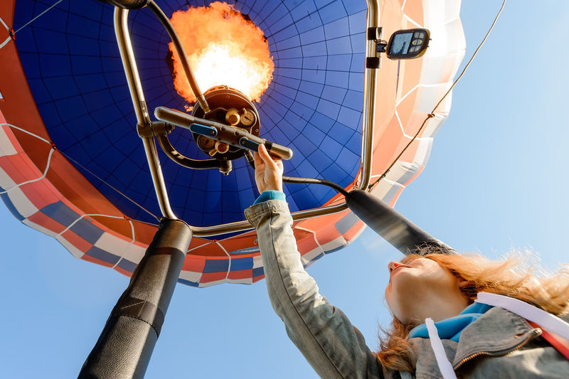 Low angle view of man hot air balloon against clear blue sky