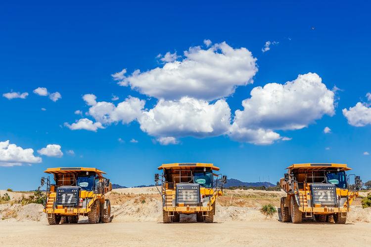 Dump trucks against cloudy sky
