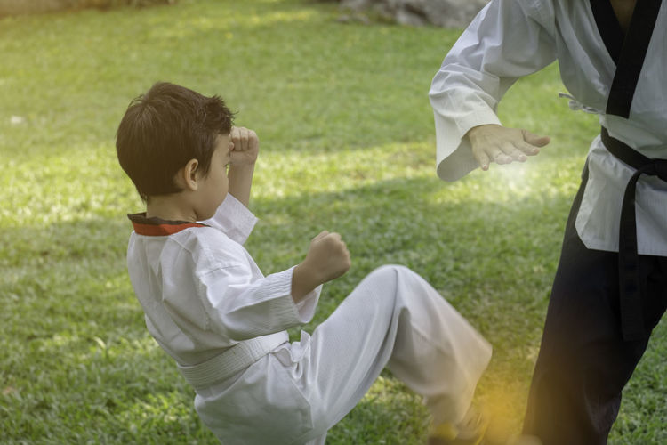 Boy and man practicing karate on field