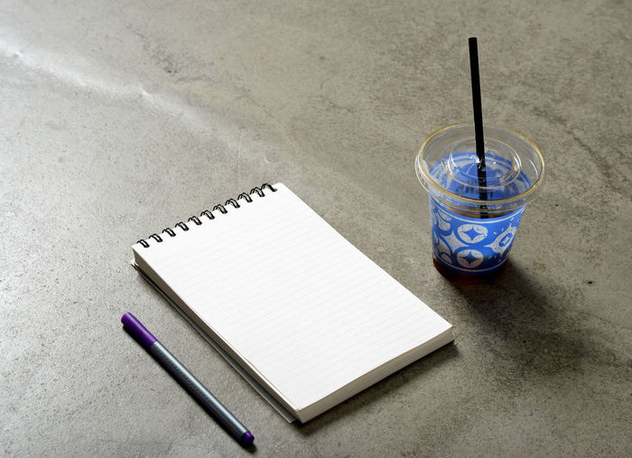 High angle view of note pad with drink on table