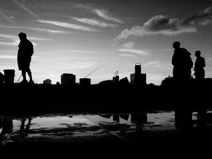 Silhouette people standing by river at sunset