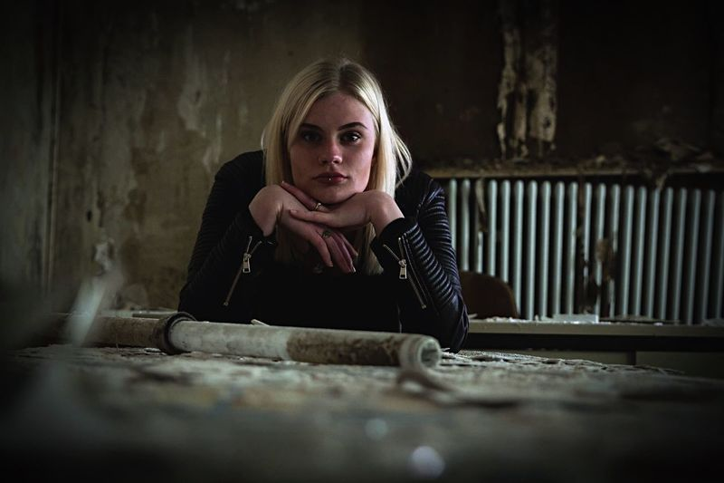 Portrait Of Young Woman Sitting In Abandoned Room
