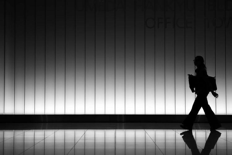 Silhouette man walking on tiled floor against wall