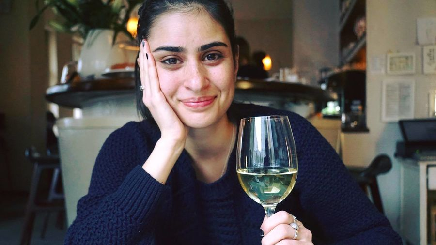 Close-up portrait of smiling beautiful woman with white wine at restaurant