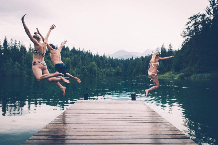 Full length of friends jumping in lake against sky