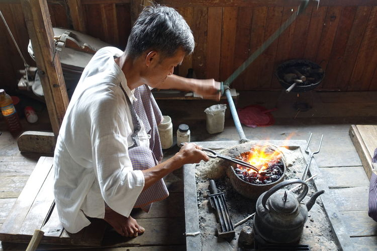 Silversmith at work in Inle Lake, Myanmar Artisan Traditional Culture Burmese Flame Heat - Temperature Indoors  Inle Lake Inle Lake, Shan State, Myanmar Men Myanmar One Man Only One Person Preparation  Real People Silversmith Silverworks Stove