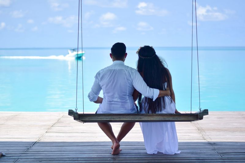 Rear view of couple sitting on swing at beach