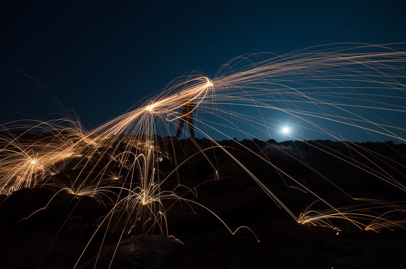 Man making wire wool at beach against clear sky at night