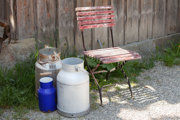 Milk cans and an old wooden chair Agriculture Barn Chair Dairy Dairy Farm Day Delivery Drink Farm Metal Milk Milk Can No People Old-fashioned Outdoors Plank Retro Rural Rural Scene Summer Waiting Weathered Wooden