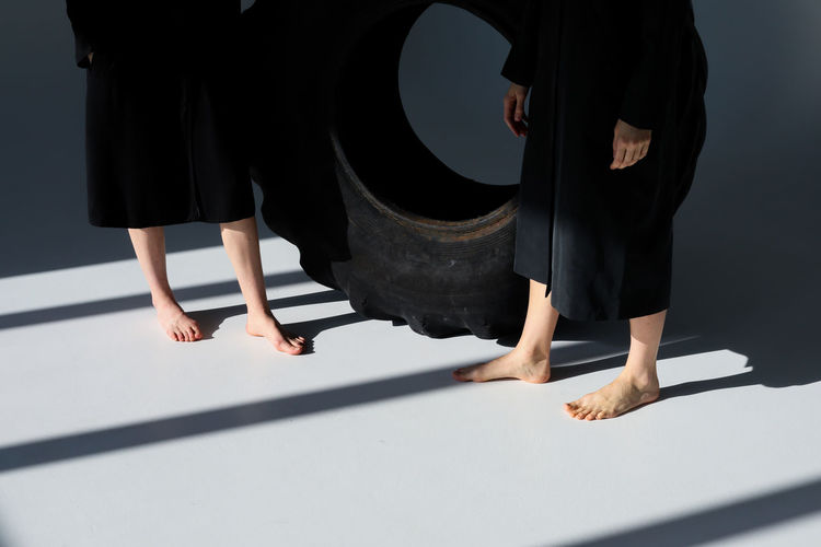 People Lifestyles Women Standing Real People barefoot Human Foot Human Leg Leisure Activity Body Part Group Of People Indoors  Sunlight Low Section Tire Light And Shadow Sunlight Studio Shot Black Minimalist Fashion Fashion Photography Gray Background Gray Casual Clothing Style Stylish Shadow