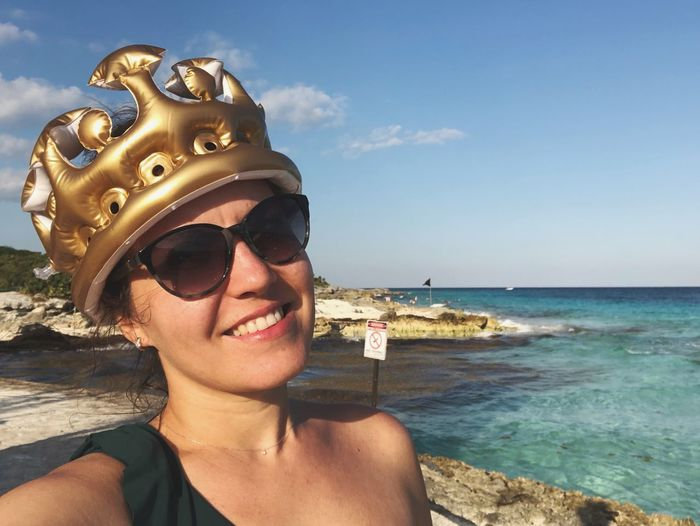 Portrait of young woman wearing inflatable crown at beach against sky