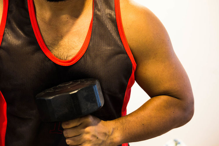 Midsection Of Man Exercising With Dumbbell Against White Background