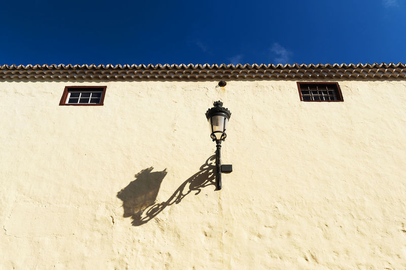 Low angle view of gas light with shadow on building