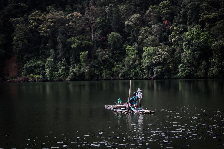 People rowing boat in lake against trees