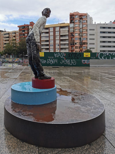 Man with sculpture in city during rainy season