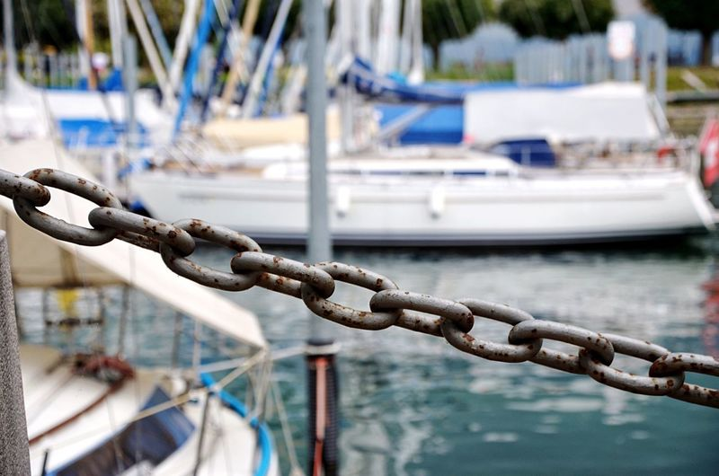 Close-up of rope tied to moored at harbor