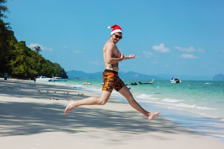 Shirtless man wearing santa hat while jumping on sand against sea at beach