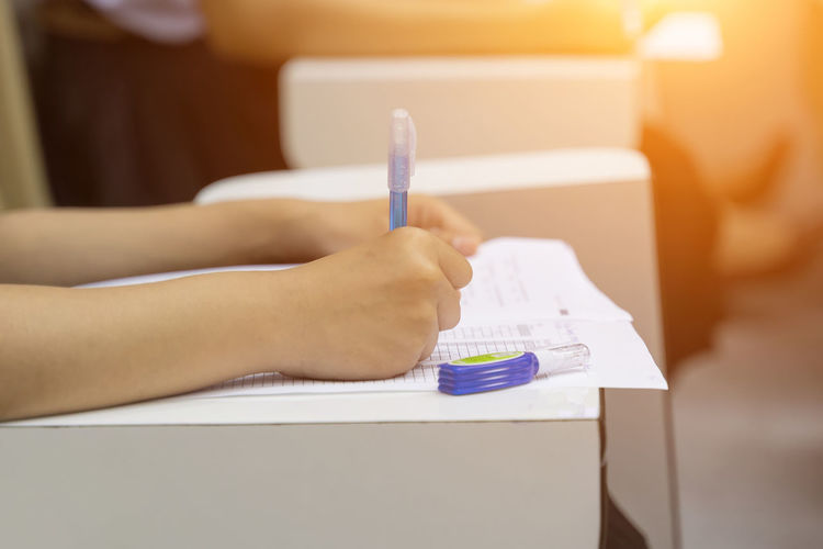 Examination Adult Childhood Close-up College4 Education Exam Focus On Foreground Hand Holding Human Body Part Human Hand Human Limb Indoors  Midsection Note Pad One Person Pen Side View Sitting Table University Women Writing