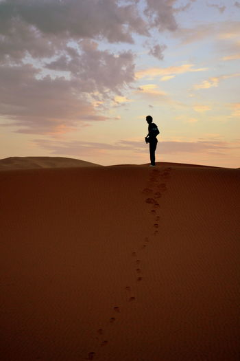 Silhouette Young Man Standing On Desert Against Cloudy Sky During Sunset