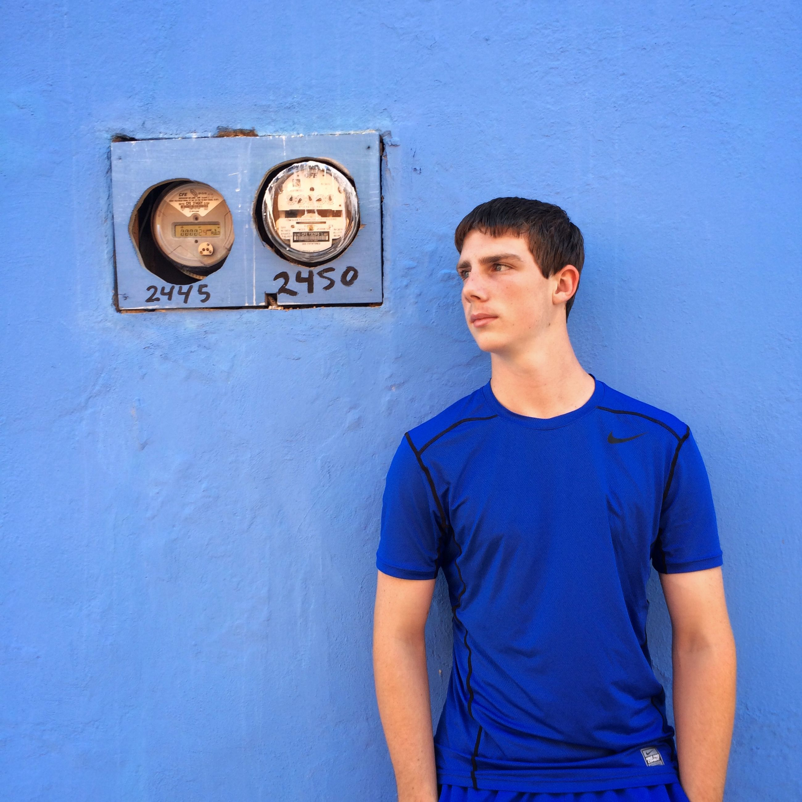 casual clothing, young men, communication, standing, waist up, lifestyles, front view, young adult, wall - building feature, leisure activity, person, three quarter length, portrait, text, blue, copy space, technology, looking at camera