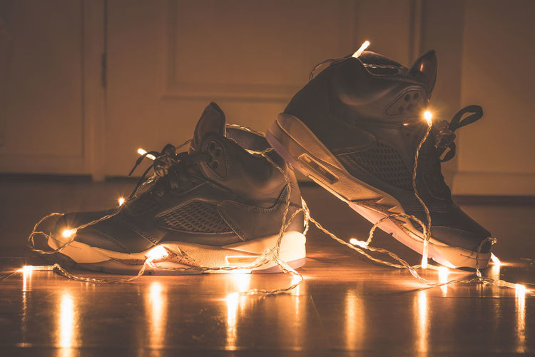 Shoes with illuminated string lights on floor at home