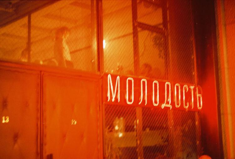 Close-up of illuminated text on glass window at night