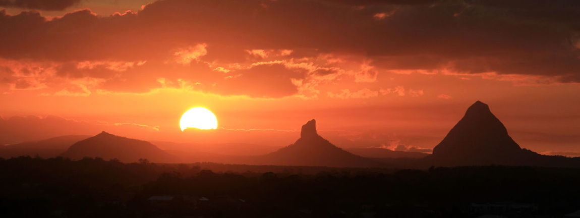 Sunset at the Glass House Mountains Glasshouse Mountains Astronomy Beauty In Nature Cloud - Sky Day Dramatic Sky Landscape Mountain Nature No People Orange Color Outdoors Scenics Silhouette Sky Sun Sunlight Sunset Tranquil Scene Tranquility Travel Destinations