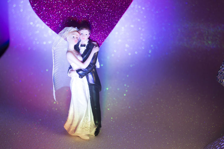 Full length of couple standing on purple wall