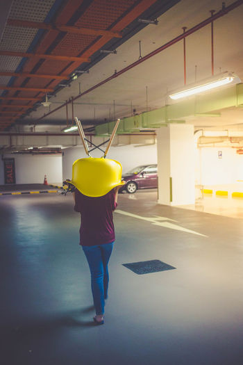 Items required for random fun - Yellow Chair - Empty Carpark - Camera Adult Architecture Built Structure Chair Empty Carpark Full Length Illuminated Indoors  One Person People Real People Rear View Standing Underground Car Park Woman Yellow Yellow Chair