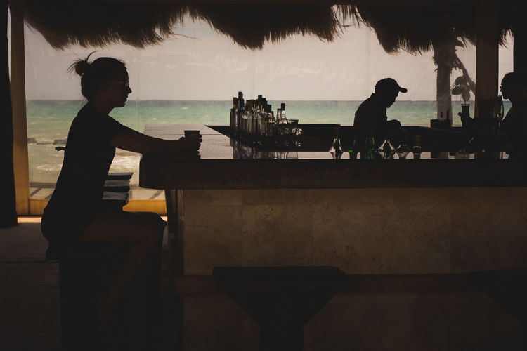 Bar Beach Beauty In Nature Day Friendship Group Of People Horizon Over Water Leisure Activity Lifestyles Men Nature Ocean Outdoors People Real People Scenics Silhouette Sitting Sky Standing Togetherness Tree Vacations Water Women