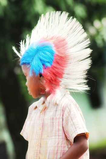 Close-up of boy wearing colorful wig while standing at park