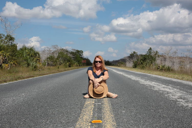 Portrait Of Woman Sitting On Empty Road Against Sky